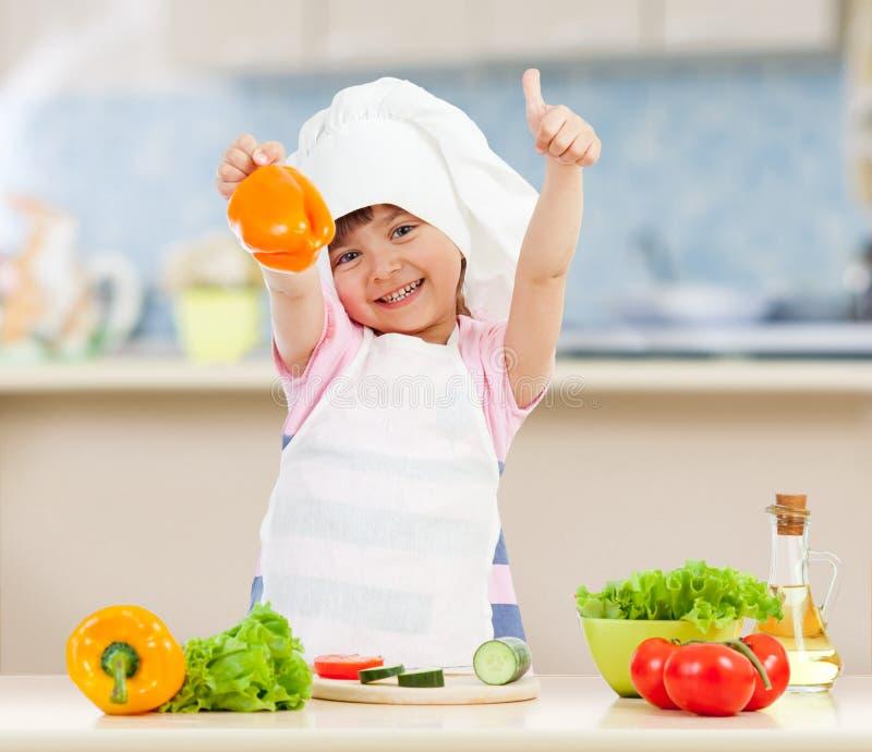 准备健康食物的厨师女孩在厨房里 免版税图库摄影