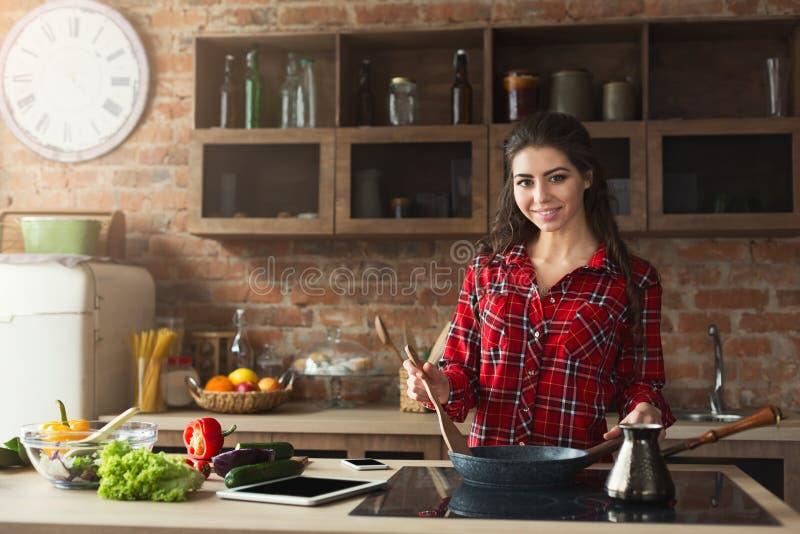 准备健康食物的愉快的妇女在家庭厨房里 库存照片