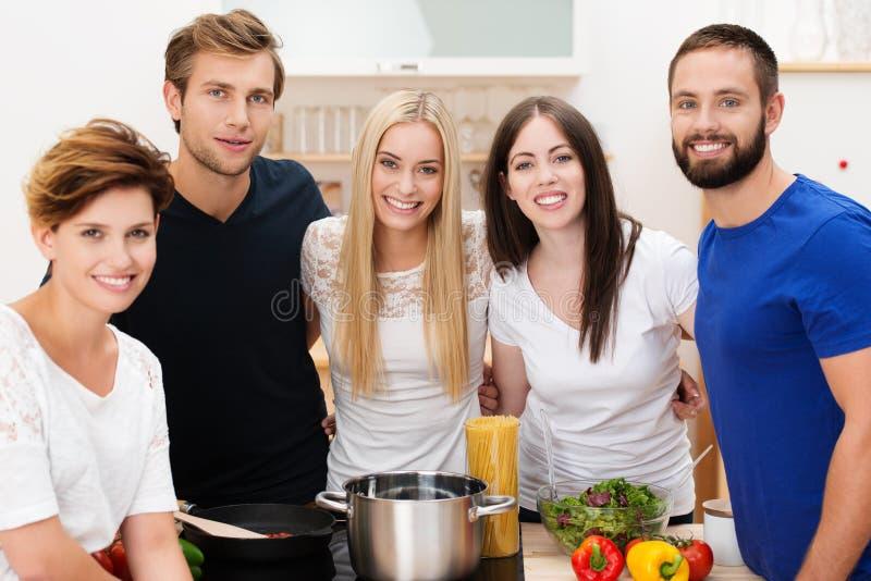 准备午餐的小组愉快的年轻朋友 库存照片