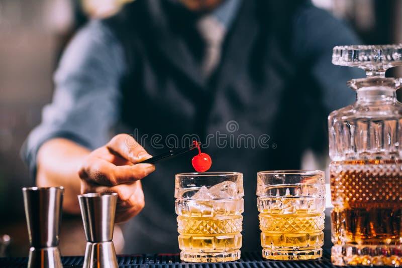 准备古板的鸡尾酒的年轻男服务员,装饰用樱桃 葡萄酒被过滤的图象 免版税图库摄影