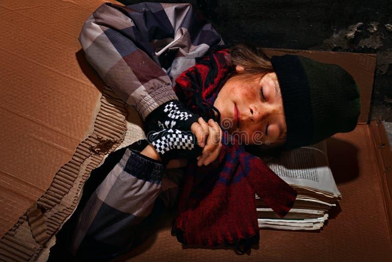 准备可怜的叫化子的男孩睡觉在街道上-盖与 免版税库存照片