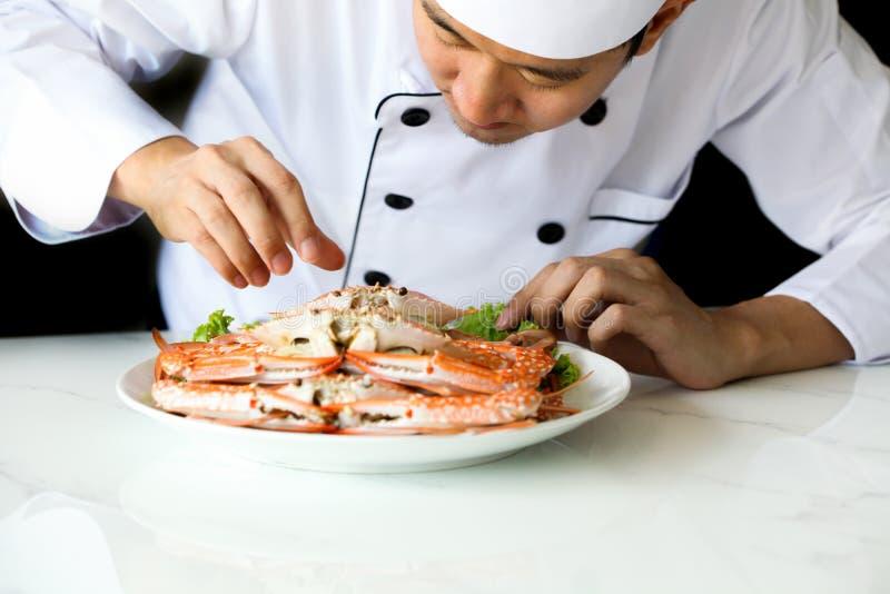 准备和装饰与菜的亚裔厨师烤螃蟹海鲜膳食 库存图片