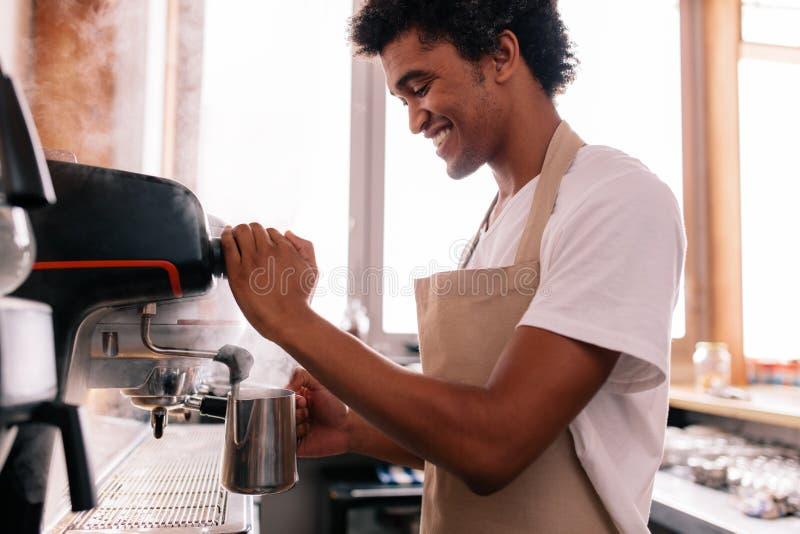准备咖啡的愉快的年轻人在柜台 库存照片