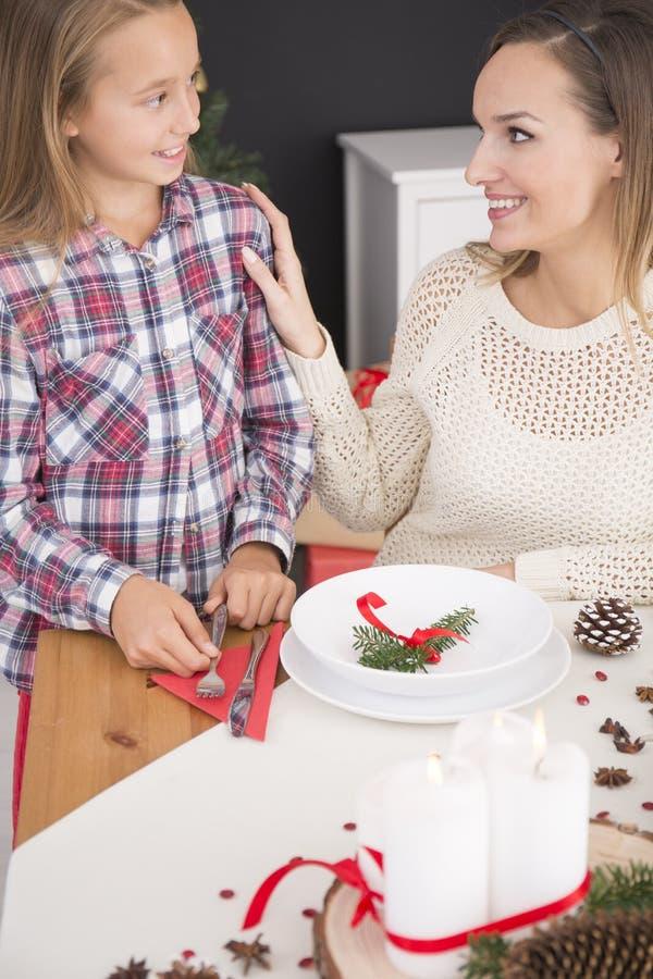 准备圣诞节桌的母亲和女儿 免版税库存图片