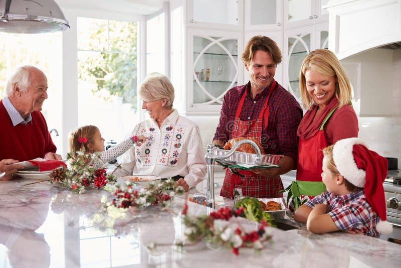 准备圣诞节膳食的大家庭小组在厨房里 库存图片