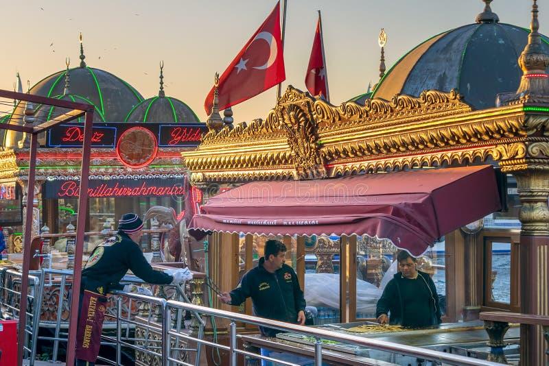 准备在一条传统快餐浮动的小船服务鱼三明治的厨师食物在Eminonu,伊斯坦布尔,土耳其 图库摄影