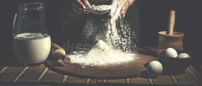 准备在木桌上的人面团在面包店关闭  复活节面包的准备 免版税库存图片