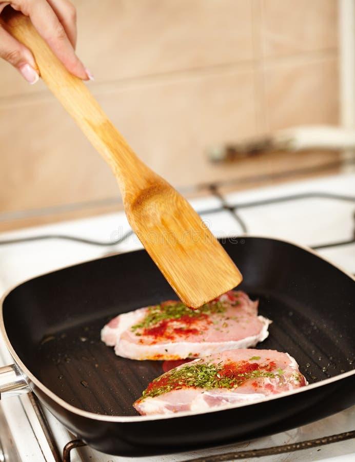 准备在煎锅的Cokk的手一个加香料的猪排 库存照片