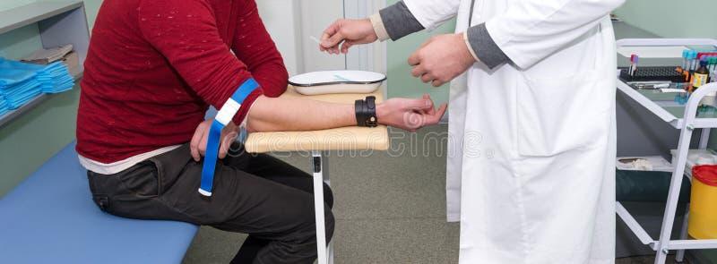 准备在采取的验血医疗技术员的准备从患者的一个血样前 库存照片