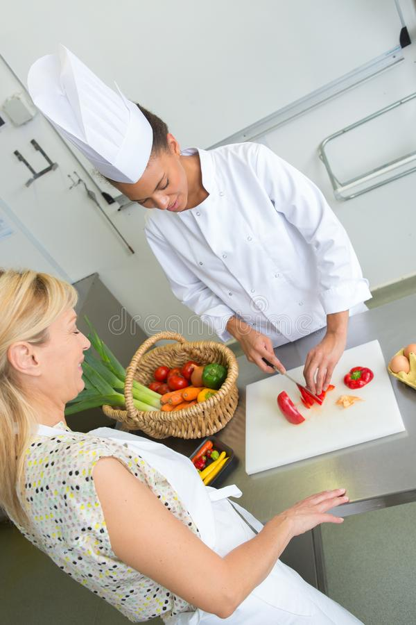 准备在餐馆厨房的友好的微笑的女性厨师食物 免版税库存图片