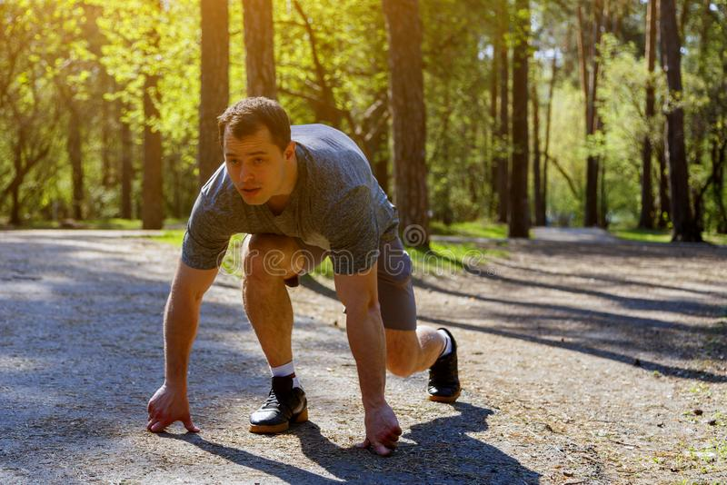 准备坚定的白种人的短跑选手开始赛跑在路在公园 库存照片