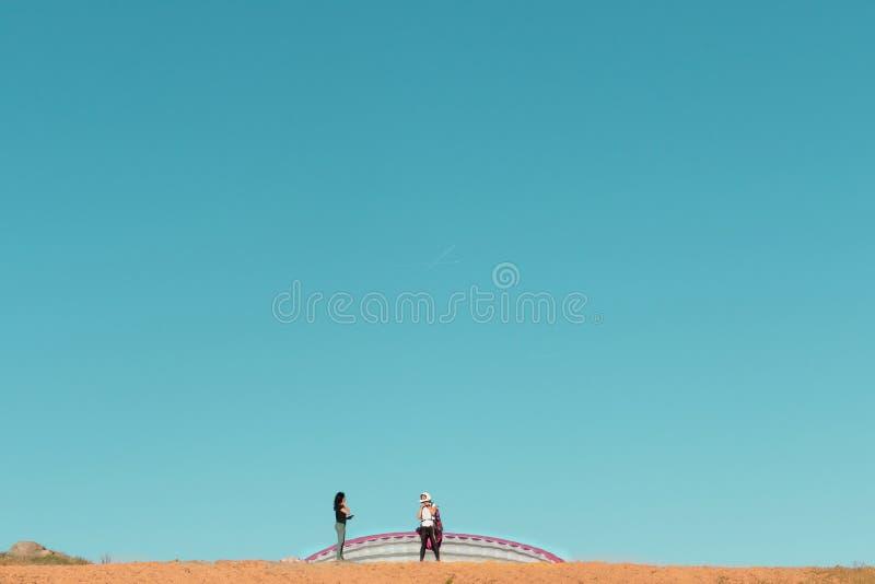 准备女性滑翔伞的飞行员离开谈话与妇女 库存照片
