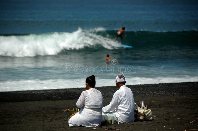 准备好一对年长巴厘语的夫妇在海滩的早晨仪式 免版税库存图片