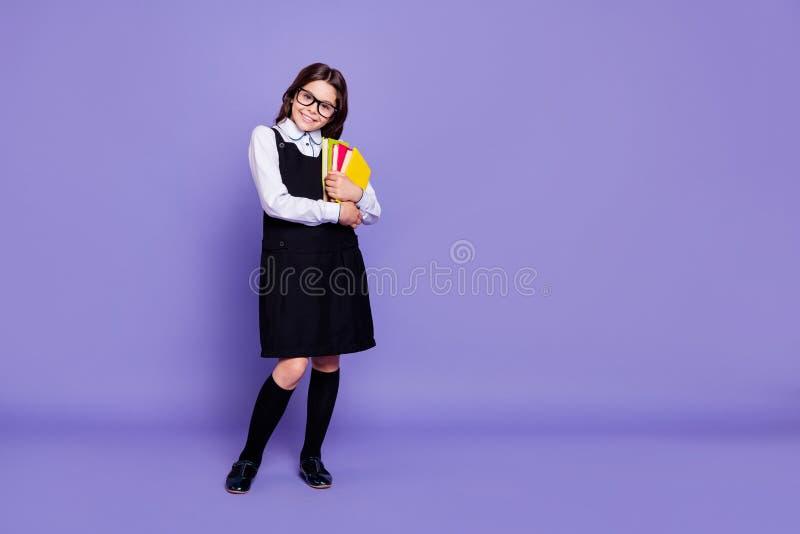 准备好全长身体尺寸观点的好可爱的快乐的聪明的有波浪头发的青春期前的女孩把举行分类  库存照片