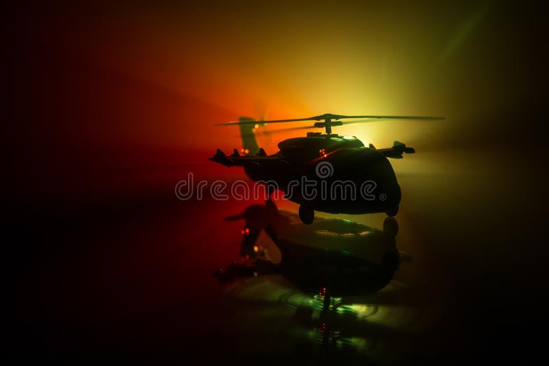 准备好军用直升机的剪影从冲突区域飞行 有起动在沙漠的直升机的装饰的夜英尺长度与 免版税库存照片
