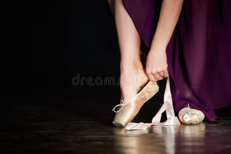准备好年轻的芭蕾舞女演员一个古典舞蹈 女孩佩带的点穿上鞋子在黑暗的背景的特写镜头在低调 库存图片