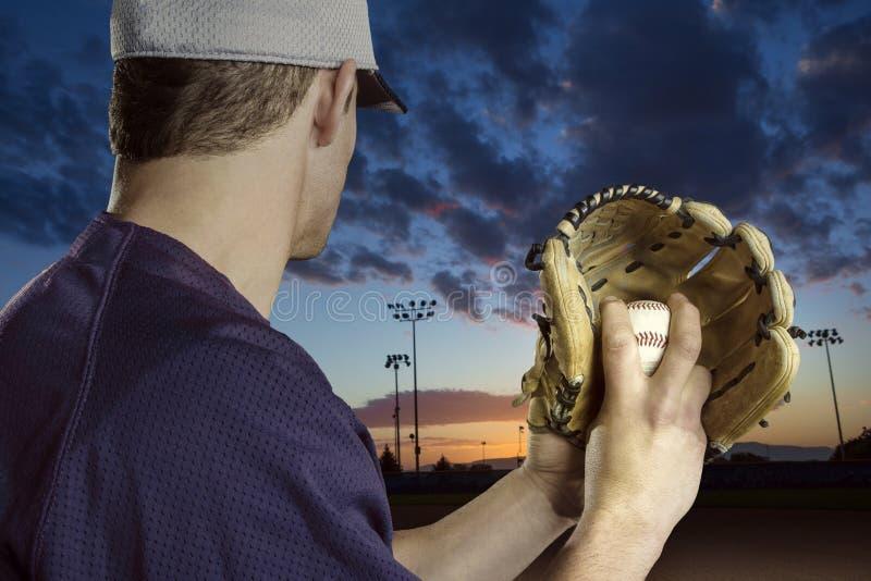 准备好棒球的投手参加晚上棒球比赛 免版税图库摄影