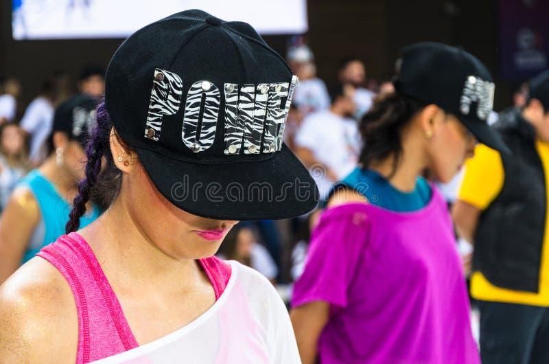 准备好的年轻女人跳舞与说力量的盖帽 库存图片