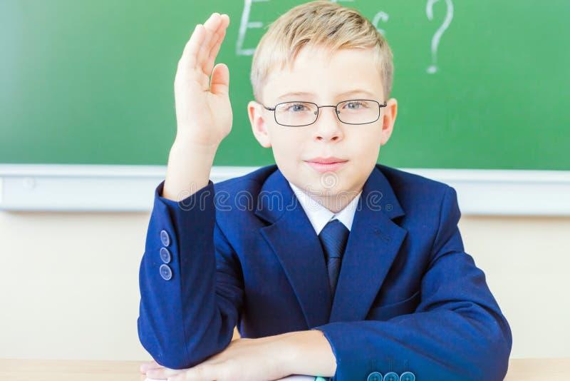 准备好的男小学生回答和被举的手  免版税库存照片