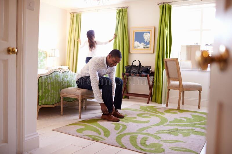 准备好年轻多种族的夫妇在旅馆客房 免版税库存照片