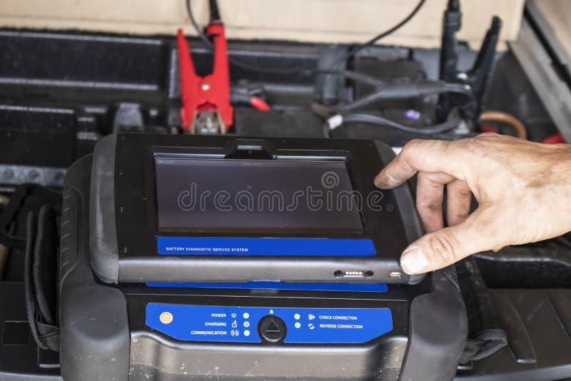 准备好Repairmans肮脏的手接触在多灰尘的流动诊断单元充电的汽车电池的显示器有被弄脏的cli的 免版税库存照片