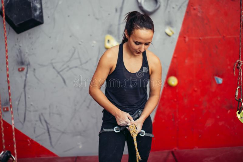 准备妇女的登山人栓在结的绳索和上升 轴上升的设备冰的山 免版税库存图片