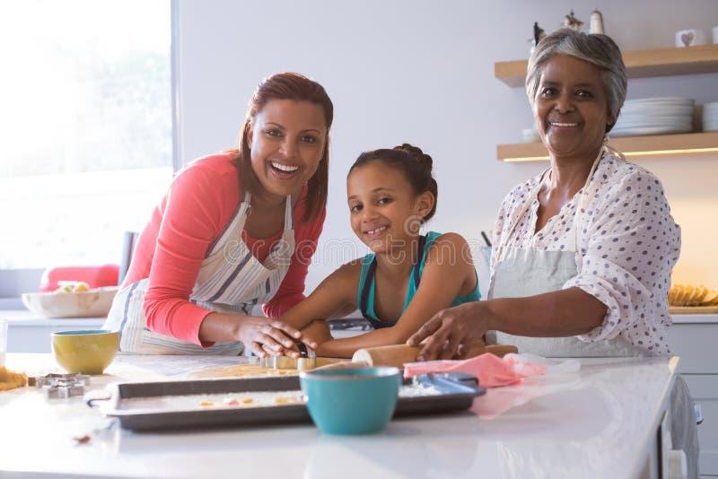 准备姜饼的愉快的多代的家庭在厨房里 免版税图库摄影