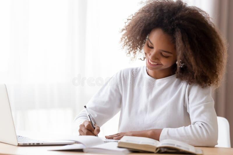 准备学校家庭作业的微笑的非裔美国人的青少年的女孩,使用膝上型计算机 免版税库存图片