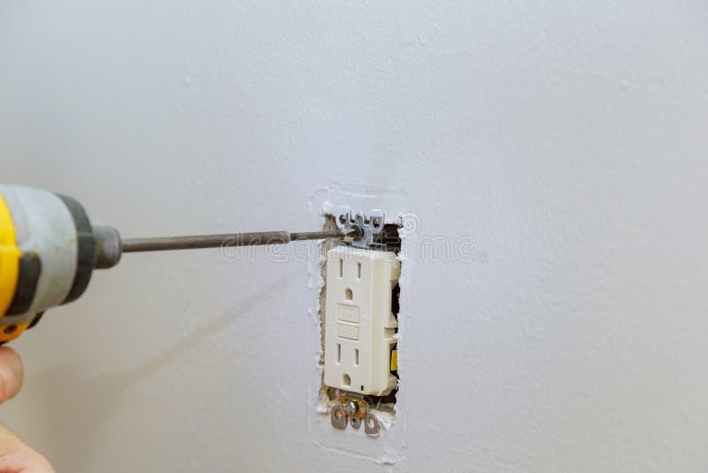 准备安装一个电子出口,检查螺丝的紧固 免版税图库摄影
