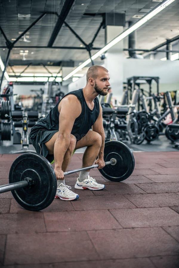 准备对deadlift在他的头的肌肉健身人杠铃在现代健身俱乐部 功能训练 夺取锻炼 免版税库存图片
