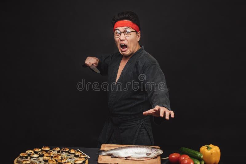 准备寿司的呼喊的疯狂的空手道人 免版税库存照片