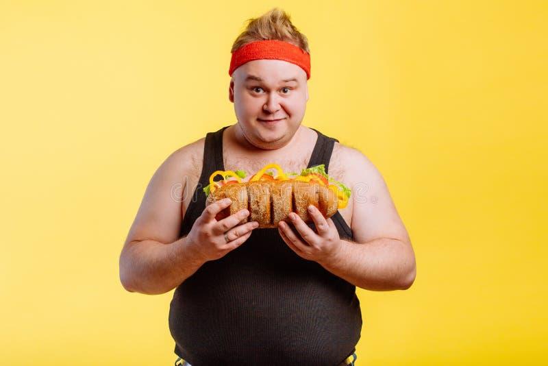 准备愉快的人吃汉堡和看照相机 免版税库存图片