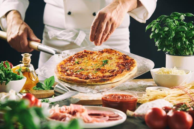 准备意大利比萨的厨师使用桨 库存图片