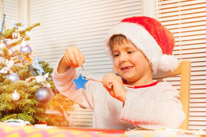 准备手工制造圣诞节装饰品的男孩 免版税库存照片