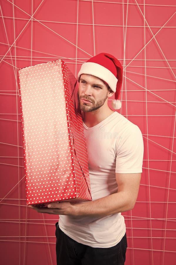 准备打开您的礼物 圣诞节假日庆祝 人英俊的不剃须的圣诞老人帽子举行礼物盒 r 库存照片