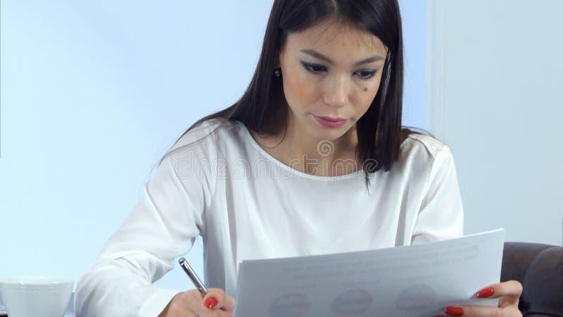 准备报告和做笔记的年轻繁忙的妇女坐在咖啡馆 免版税库存照片