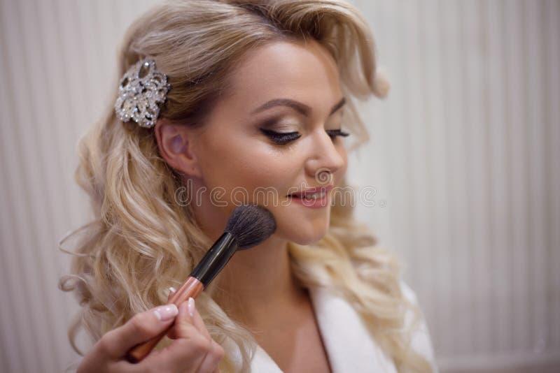 准备新娘的化妆师在婚礼前在一个早晨 免版税库存图片