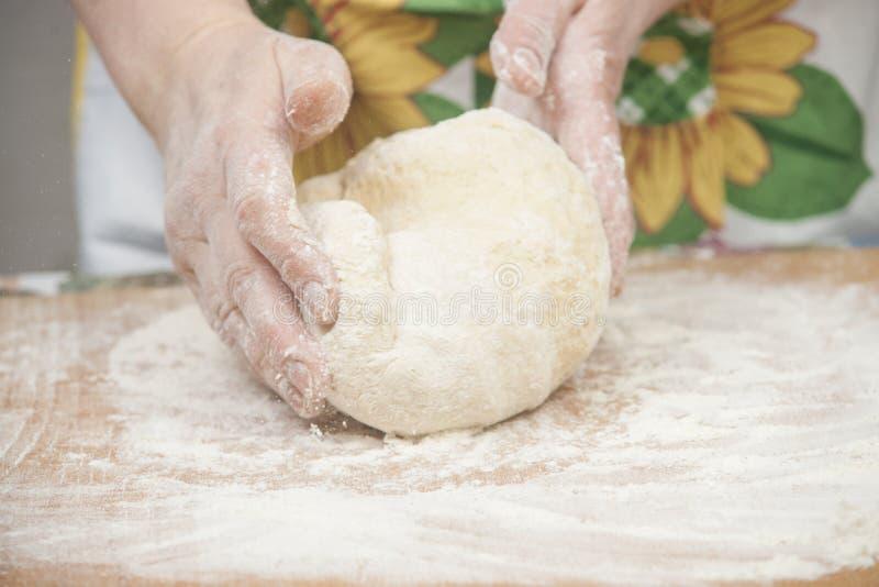 准备新鲜的发酵面团的妇女的手 免版税图库摄影