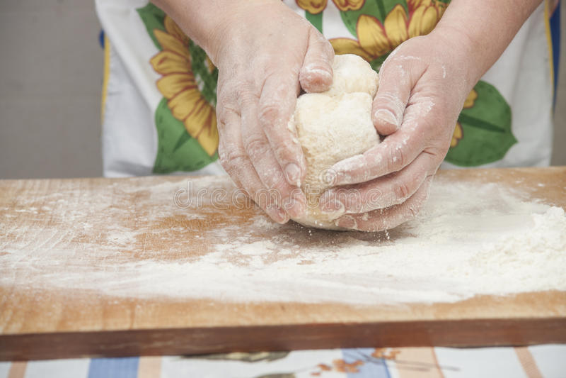 准备新鲜的发酵面团的妇女的手 免版税库存照片