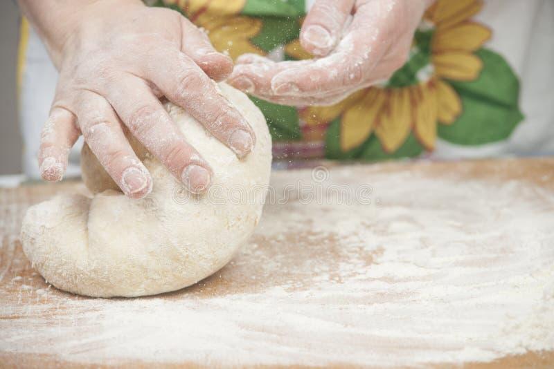 准备新鲜的发酵面团的妇女的手 免版税库存图片