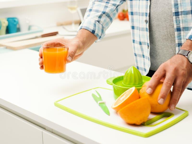 准备新鲜的橙汁的人 免版税库存图片