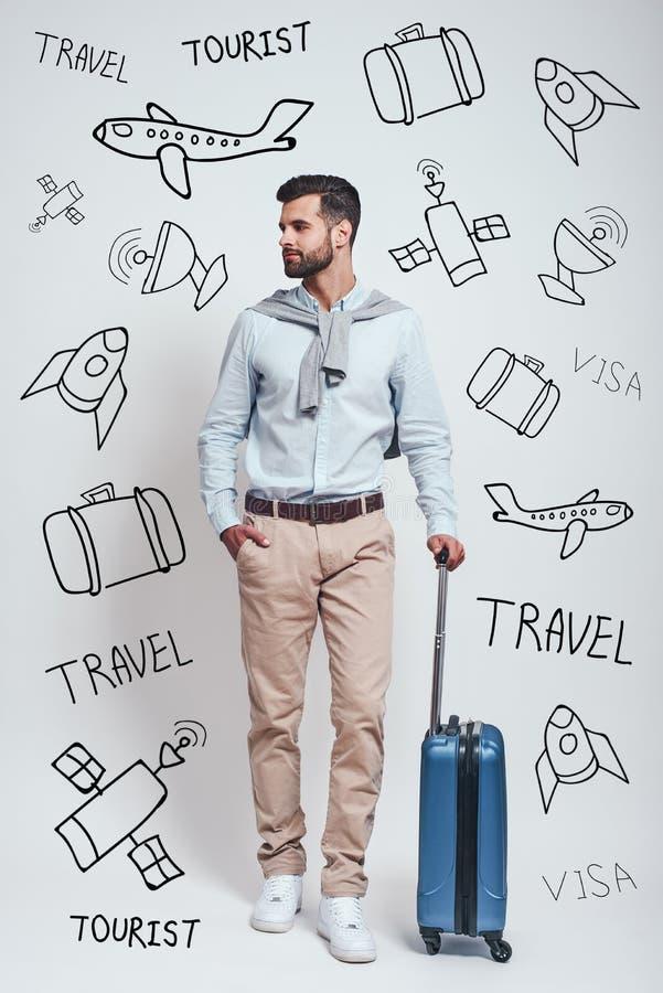 准备旅行 等待带着手提箱的全长英俊的有胡子的年轻人,当站立反对灰色背景时 库存照片