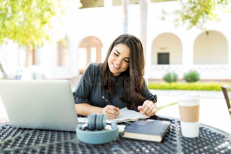 准备日程表的妇女,当看膝上型计算机在庭院里时 免版税图库摄影
