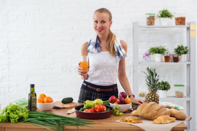 准备晚餐在厨房里,饮用的汁液概念烹调,烹饪,健康生活方式的妇女 库存图片
