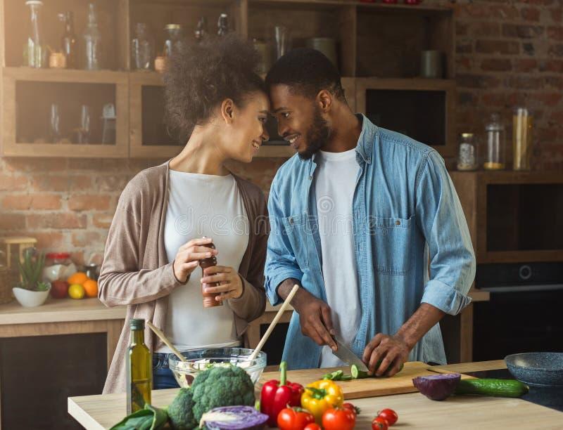 准备晚餐的爱恋的非裔美国人的夫妇在厨房里 图库摄影
