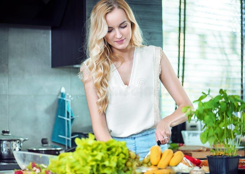 准备晚餐盘的白肤金发的妇女 库存照片