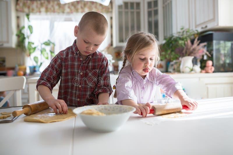 准备曲奇饼的孩子在厨房里 库存图片