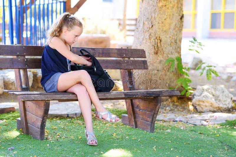 准备有学校用品的少年女孩背包 免版税库存照片