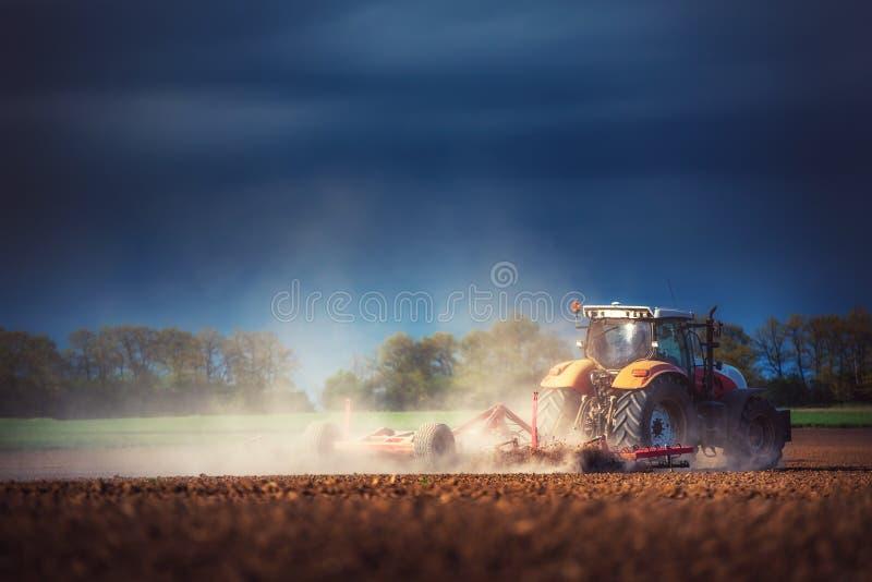 准备有温床耕地机的拖拉机的农夫土地 库存照片