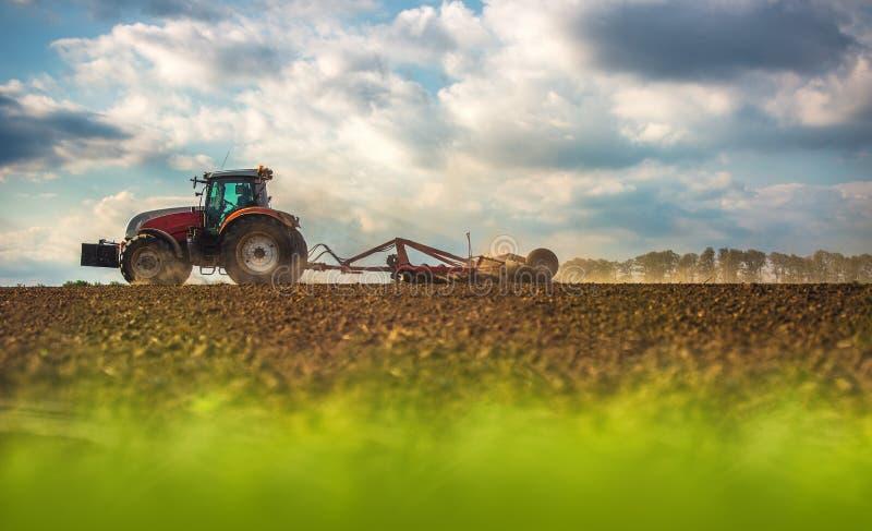 准备有温床耕地机的拖拉机的农夫土地 库存图片